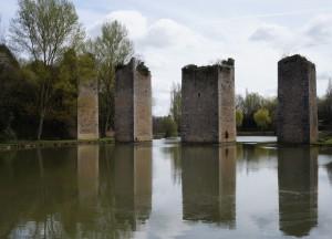 Lussac-les-Chateaux. L'étang et les piliers du pont-levis.