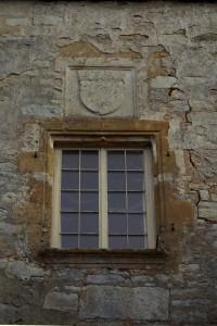 Charroux, abbaye Saint-Sauveur, porte de l'Aumônerie, détail de la fenêtre et de l'armoirie royale.