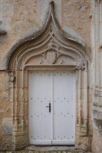 Ayron, château, porte d'entrée avec architrave en accolade armorié.